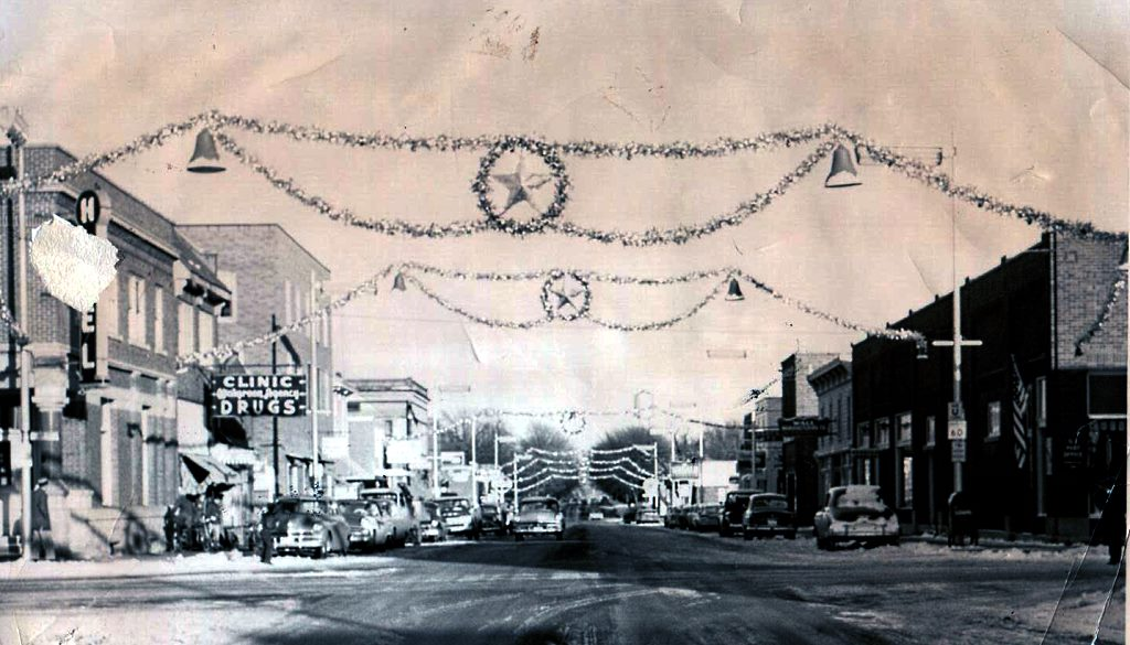 CHRISTMAS STREET DECORATIONS cross 3rd Avenue (then Minnesota State Highway #60) from 10th Street to 12th Street. At right, where Sweet Fields is now located, was the Post Office, as noted by the American flag.